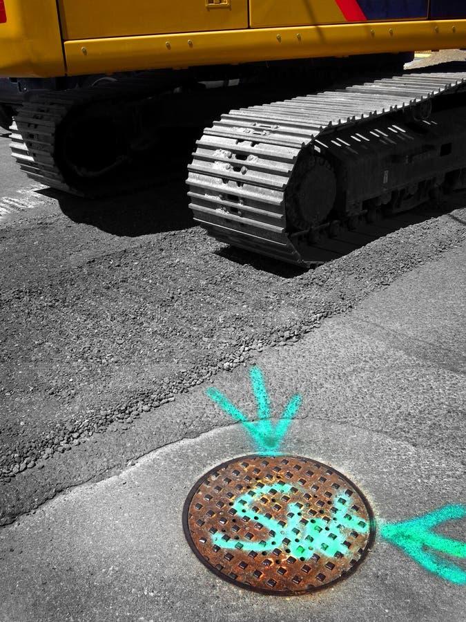 Attrezzatura pesante dell'escavatore a cucchiaia rovescia sulla via con la copertura di botola della fogna fotografia stock libera da diritti