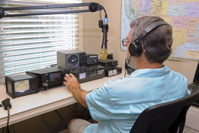 Attrezzatura radiofonica di funzionamento dell'uomo fotografia stock