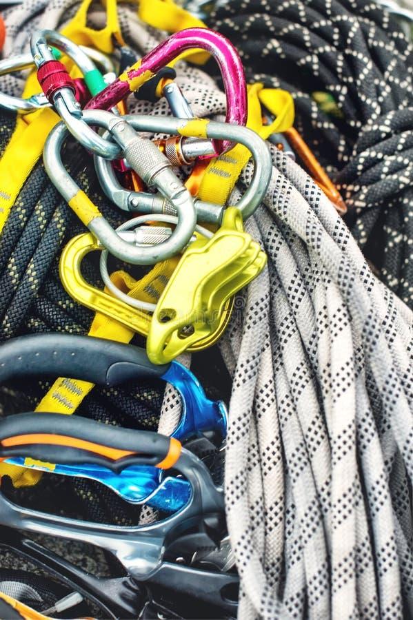 Attrezzatura rampicante utilizzata - carabiner senza graffi, martello rampicante, casco bianco e corda grigia, rossa, verde e ner immagini stock libere da diritti