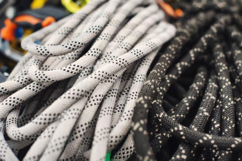 Attrezzatura rampicante utilizzata - carabiner senza graffi, martello rampicante, casco bianco e corda grigia, rossa, verde e ner fotografia stock