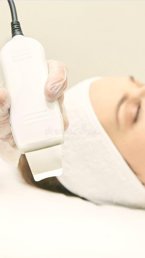 Attrezzatura ultrasonica della pelle Trattamento di cosmetologia del fronte della donna Procedura facciale della clinica della ra fotografia stock libera da diritti