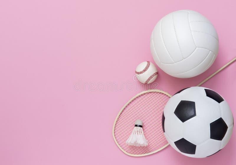 Attrezzature sportive assortite, tra cui pallacanestro, pallavolo, pallavolo, baseball, racket su sfondo rosa immagini stock libere da diritti