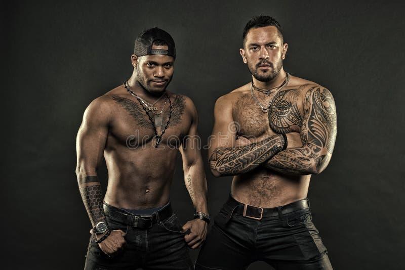 Attribut brutal de tatouage Corps tatou? par aspect hispanique attrayant brutal d'hommes Les hommes barbus montrent le torse tato images stock