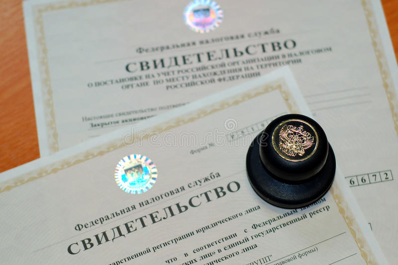 The attributes of the enterprise. On the table lay the seal of the enterprise under which the certificate of registration of the company and the assignment stock photography