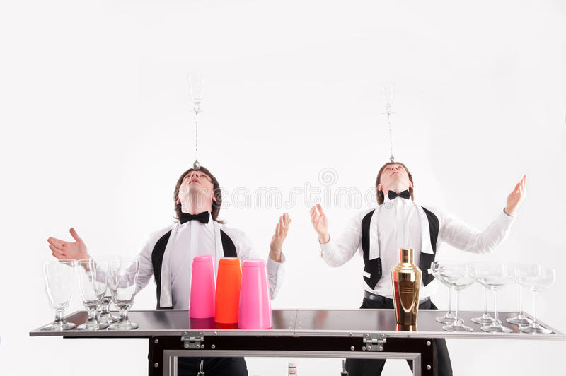 Attributes of good barman. Two handsome barmen standing near the bar counter with different glasses and shaker on it holding on their head bar spoon with empty stock images