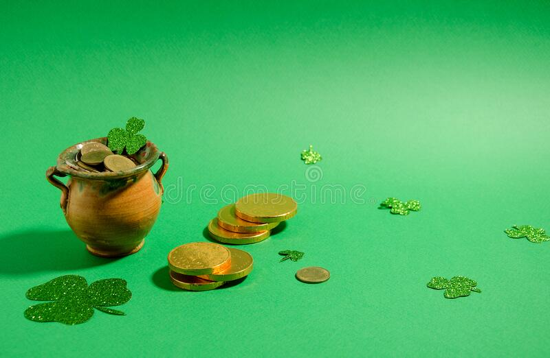Attributes St. Patrick's Day - a pot of gold stands on a green background, next to it are gold coins and clover leaflets. Horizontal background, soft royalty free stock photography