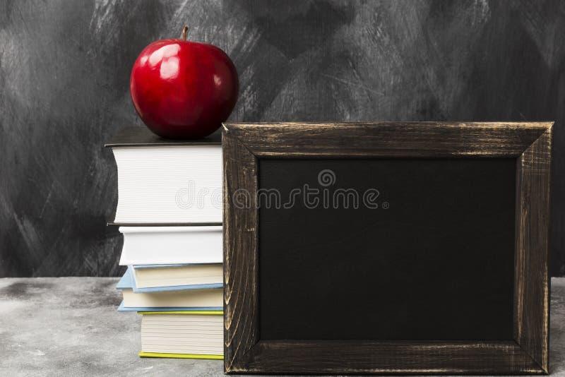 Attributi della scuola - bordo nero, libri, mela su fondo scuro immagini stock