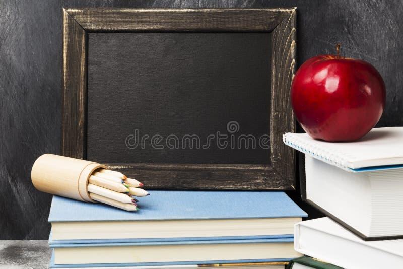 Attributi della scuola - il bordo nero, libri, ha colorato le matite, noteboo fotografie stock libere da diritti