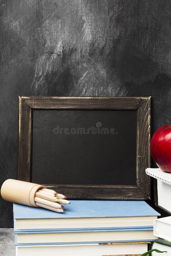 Attributi della scuola - il bordo nero, libri, ha colorato le matite, noteboo fotografia stock libera da diritti