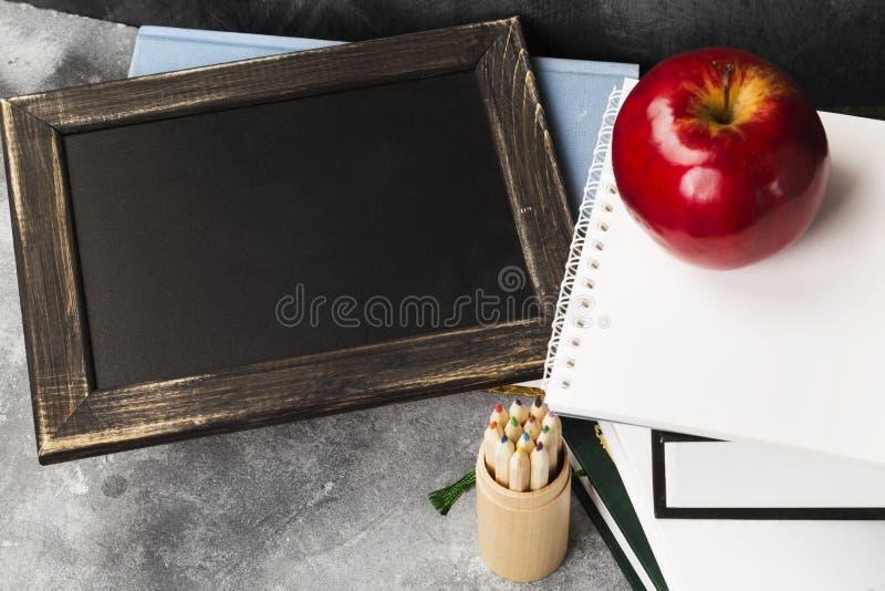 Attributi della scuola - il bordo nero, libri, ha colorato le matite, noteboo fotografia stock