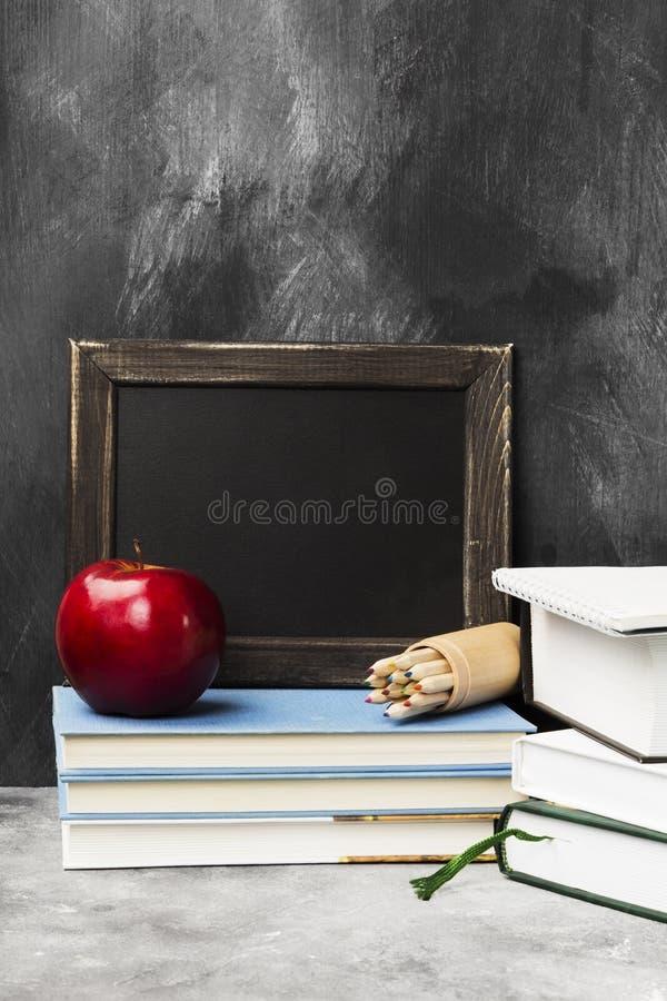 Attributi della scuola - il bordo nero, libri, ha colorato le matite, noteboo fotografie stock