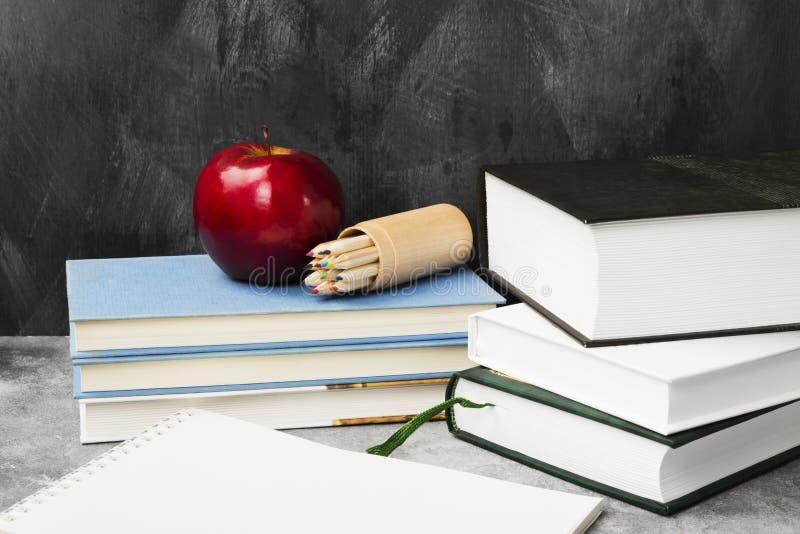 Attributi della scuola - libri, matite colorate, taccuino, mela sopra fotografia stock