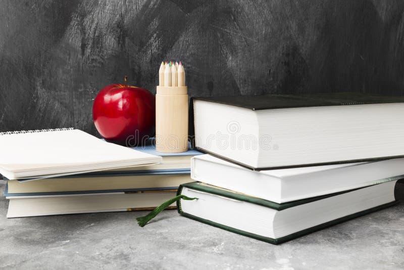 Attributi della scuola - libri, matite colorate, taccuino, mela sulla d immagini stock
