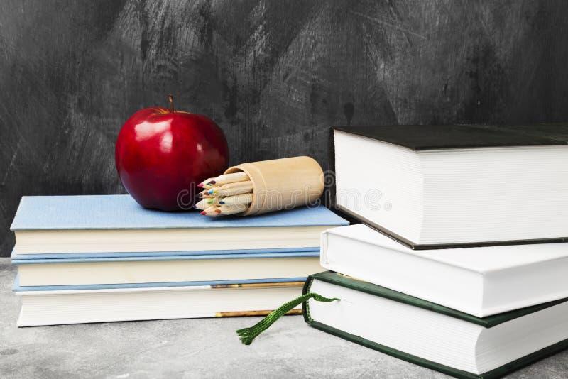 Attributi della scuola - libri, matite colorate, taccuino, mela sulla d immagine stock