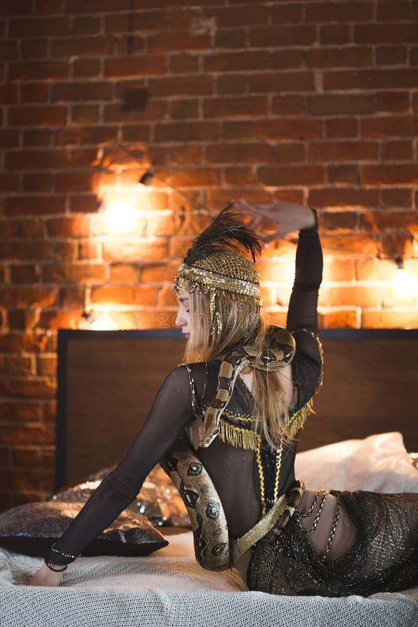 Attrice elegante del circo che posa con un pitone sul letto immagine stock libera da diritti