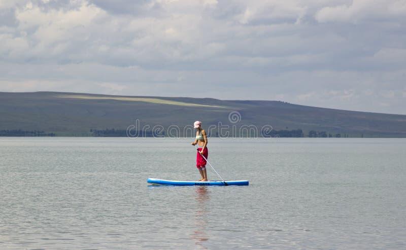 Aturdiendo la silueta de una muchacha hermosa que flota encendido en la tabla hawaiana foto de archivo