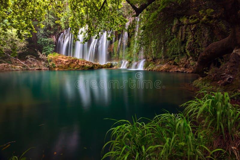 Aturdindo cachoeiras sobre um lago do emrald em profundo - floresta verde no parque natural de Kursunlu, Antalya, Turquia foto de stock