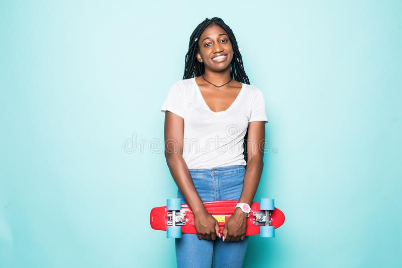 Aturdindo a jovem mulher nas cal?as de brim e nos ?culos de sol vestindo da camisa branca que levantam com sorriso no fundo azul  foto de stock