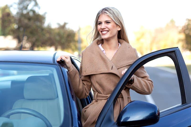 Aturdindo a mulher no revestimento marrom que entra em seu carro foto de stock royalty free