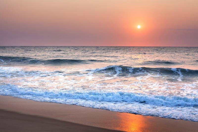 Aturdindo o por do sol ou o nascer do sol sobre o mar ou o oceano na praia, no céu roxo, nas ondas azuis, na espuma branca e na r imagens de stock