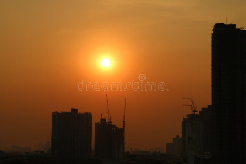 Aturdindo o sol de nivelamento brilhante no céu alaranjado profundo da cor sobre a silhueta do canteiro de obras imagens de stock royalty free