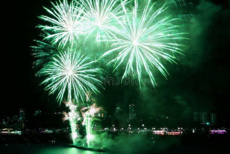 Aturdindo os fogos de artifício verde-claro da cor que explodem dentro ao céu noturno sobre a baía fotografia de stock royalty free