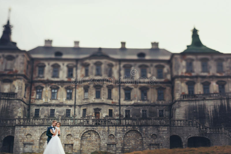 Aturdir besos casados de la pareja en el frente de un castillo viejo foto de archivo