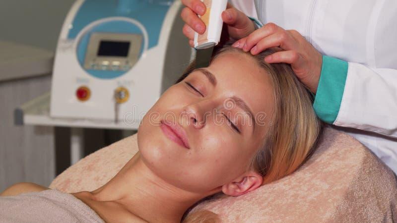 Aturdir a la mujer con la piel perfecta que consigue el tratamiento facial ultrasónico imagen de archivo