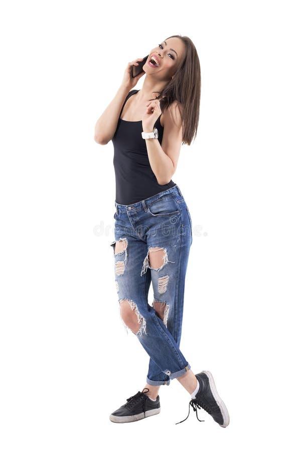 Aturdir a la mujer joven de la belleza que habla y que ríe en el pelo de giro del teléfono móvil foto de archivo libre de regalías
