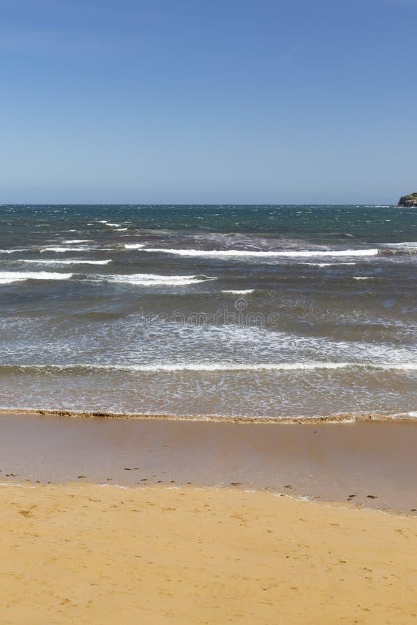 Aturdir la vista de la resaca de la calma del océano con las ondas reservadas que alcanzan la orilla arenosa y los cielos claros  fotos de archivo