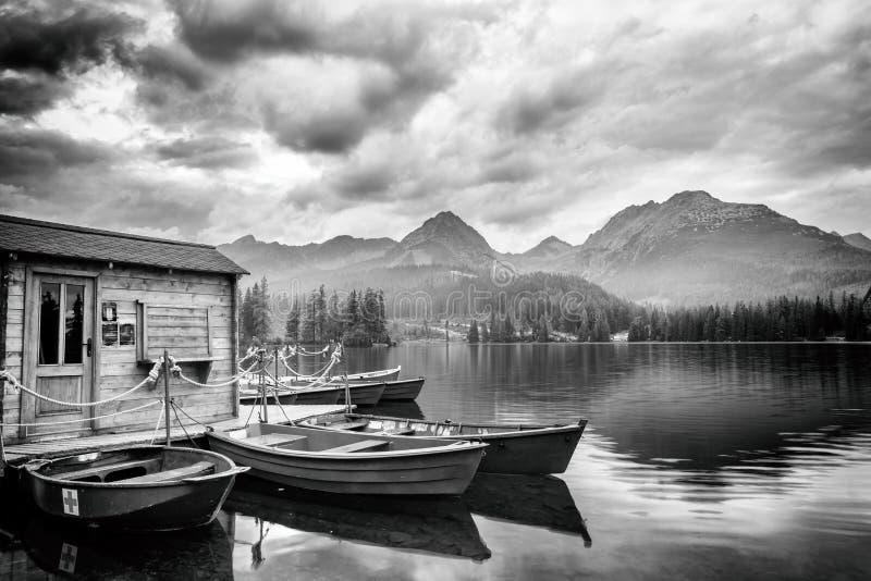 Aturdir paisaje blanco y negro con el cielo nublado, las montañas y el lago con los barcos de placer, Strbske Pleso, alto Tatras, fotografía de archivo