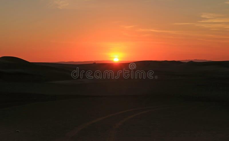 Aturdir puesta del sol sobre la duna de arena del desierto de Huacachina con la gente y el coche de playa en distancia, región de fotos de archivo