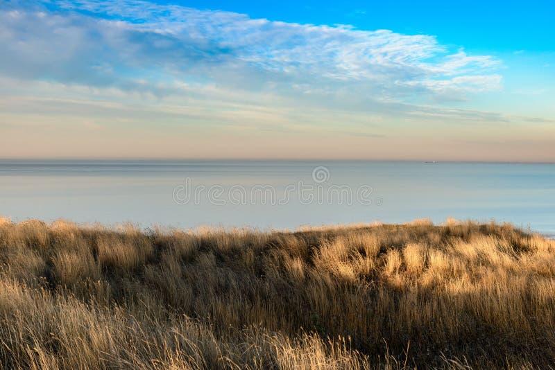 Aturdir a vista sobre a grama cobriu dunas para do horizonte de mar imagem de stock royalty free