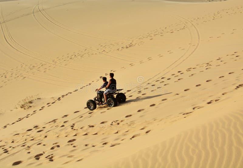 ATV的人们在沙漠 库存图片