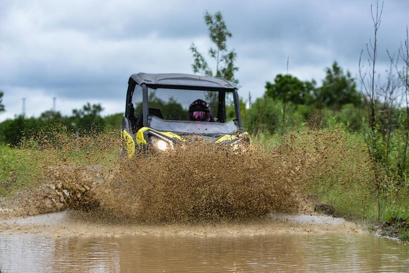 ATV brp继续前进一泥泞水坑做飞溅 免版税库存照片