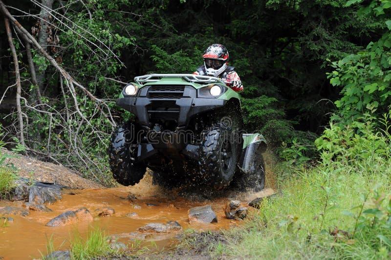 ATV in creek royalty free stock image