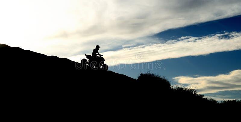 ATV dans le coucher du soleil images libres de droits
