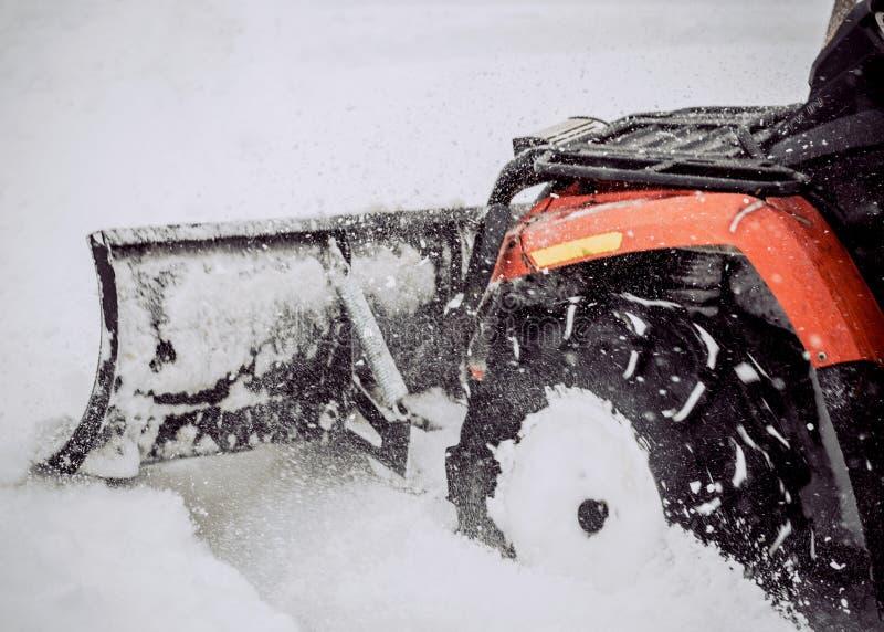 ATV en la nieve Limpieza de las calles de la nieve con un tractor foto de archivo libre de regalías