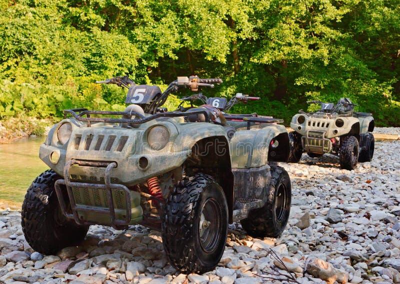 ATV estacionó en la orilla de un río de la montaña fotos de archivo