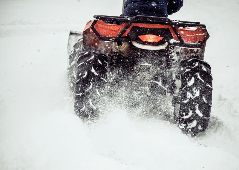 ATV glisse dans la neige Nettoyage des rues de la neige avec un tracteur photographie stock