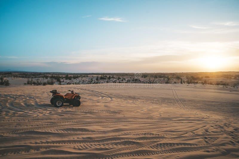 ATV-kvadratcykel framme av soluppgång i öknen ATV står i sanden på en sanddyn i öknen av Vietnam Mui Ne royaltyfria foton