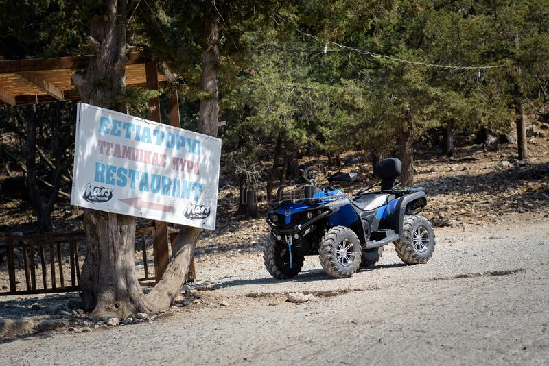 ATV motorbike is parked near entrance of traditional Greek tavern on Rhodes island. stock photos