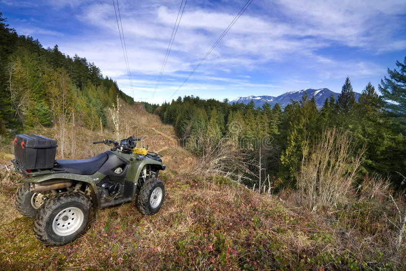 ATV parked overlooking forest. Single ATV parked on a mountain top overlooking the views of a forest and Mountain Range. Wide angle shot with good space for ad royalty free stock images