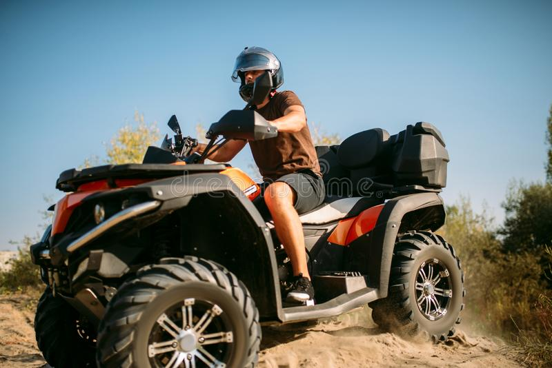 Atv rider in helmet rides on sandy road in forest stock images