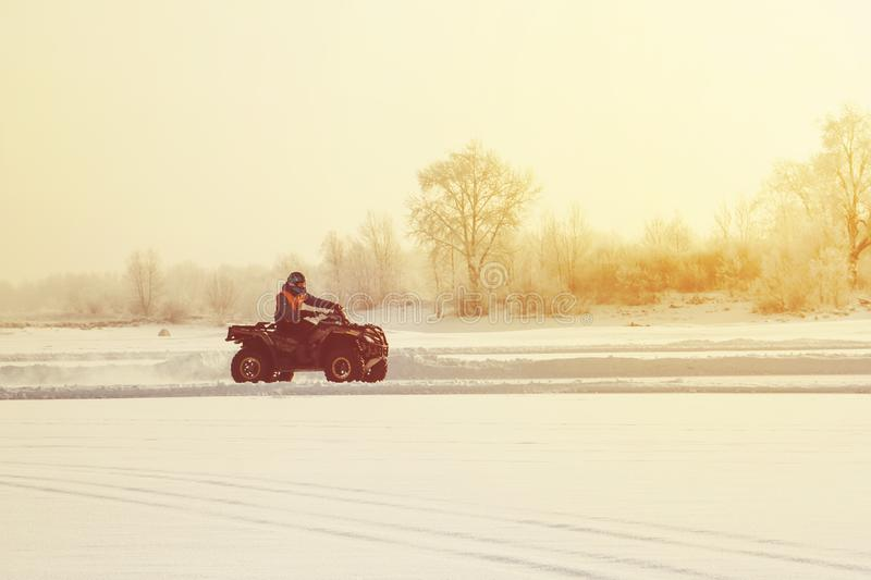 The ATV rider rides on the ice at sunset in winter royalty free stock photos