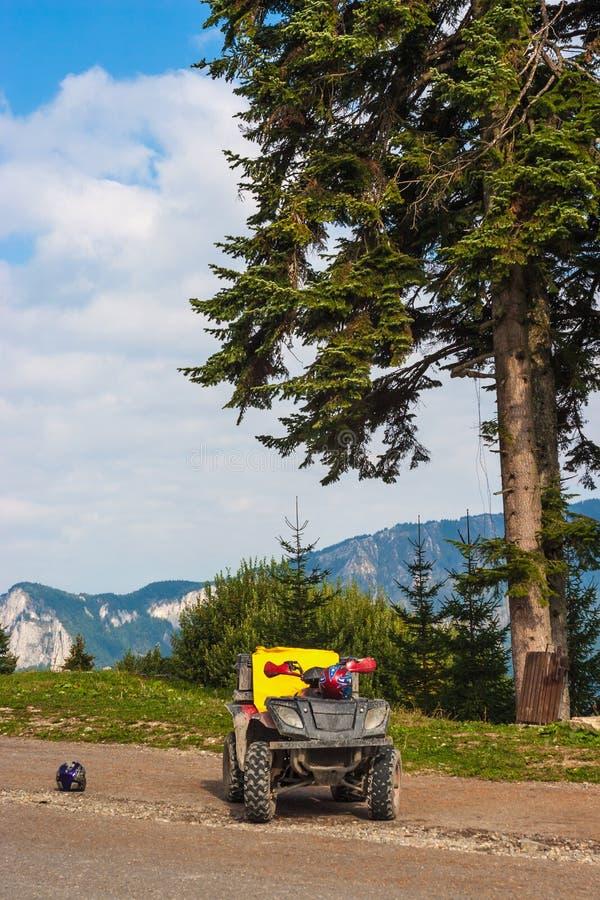 ATV-Vierlingfiets aan de kant van de weg Bergtop op de achtergrond Sparren op de linkerzijde stock fotografie