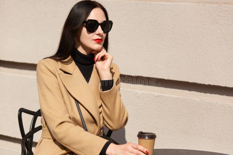 Außenaufnahme der brunette Frau mit dem langen Haar, das beige Mantel trägt, bei Tisch im Straßencafé sitzt und Mitnehmerkaffee h stockfotografie