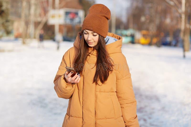 Außenaufnahme der brunette jungen Frau trägt braunen Hut und Jacke, hält Handy, liest Mitteilung, hat Spaziergang während des Win stockfotografie