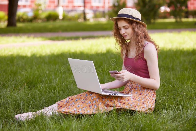 Außenaufnahme des durchdachten süßen Modells, das mit ihren modernen Geräten, unter Verwendung ihres Smartphone und Laptops, trag stockbilder