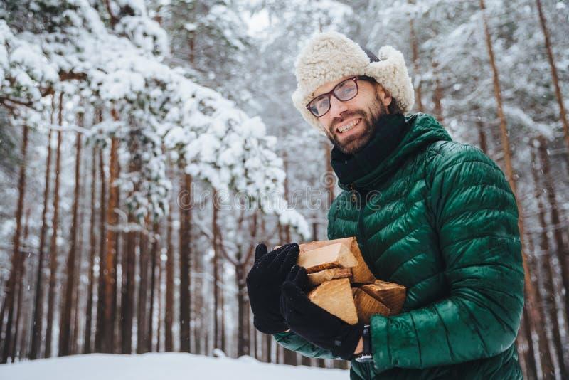 Außenaufnahme des lächelnden frohen Mannes mit Bart und dem Schnurrbart trägt Schauspiele, anork und warmer Hut, hält Brennholz,  lizenzfreies stockfoto